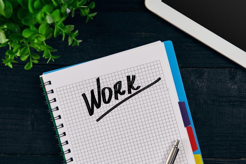 Hoogste mening van open die notitieboekje met het WERKinschrijving wordt geschreven Groen bloem, tablet, pen en notitieboekje op  stock afbeelding