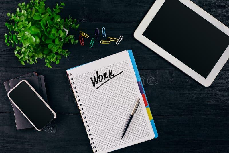 Hoogste mening van open die notitieboekje met het WERKinschrijving wordt geschreven Groene bloem, tablet, gekleurde paperclippen, stock foto