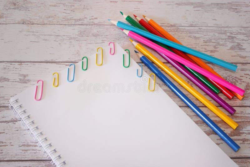 Hoogste mening van open sketchbook met blanco pagina copyspace en kleurrijke potloden en paperclippen op een houten bureau Spot o stock afbeeldingen