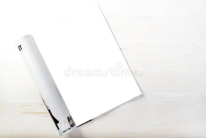 Hoogste mening van open tijdschrift met lege witte pagina's op lichte houten royalty-vrije stock afbeeldingen
