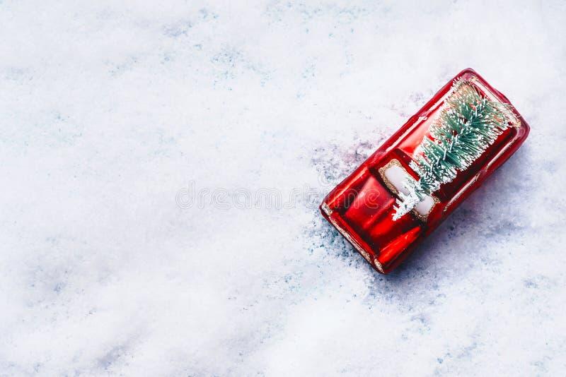 Hoogste mening van over rode stuk speelgoed retro auto met groene Kerstboom in sneeuw Het creatieve concept van de Kerstmisvakant stock foto