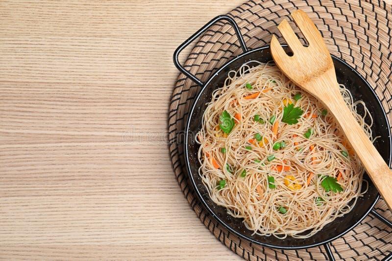 Hoogste mening van pan met heerlijke Aziatische noedels en groenten op houten achtergrond stock afbeeldingen