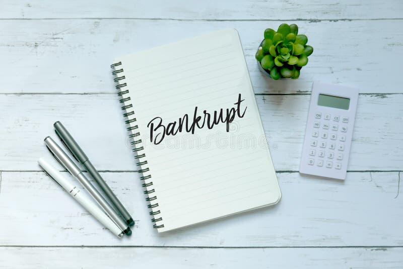 Hoogste mening van pen, calculator, installatie en notitieboekje dat met Failliet op witte houten achtergrond wordt geschreven royalty-vrije stock fotografie