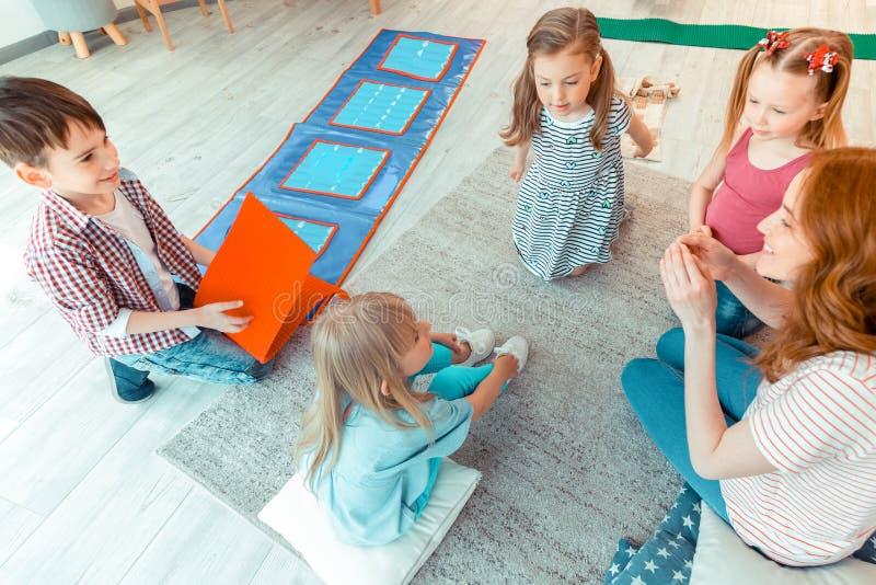Hoogste mening van positieve aardige kinderen die met een psycholoog zitten royalty-vrije stock fotografie
