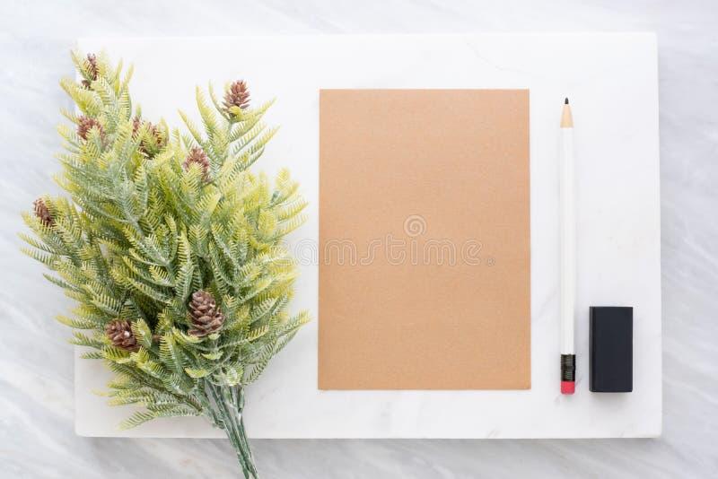 Hoogste mening van potlood, gom, sparblad en bruine blocnote op wit stock foto