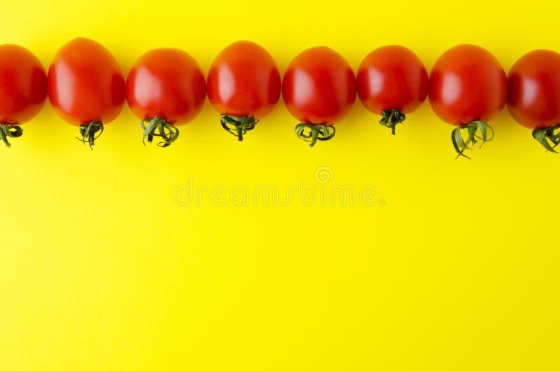 Hoogste mening van rode verse tomaten, lijn van heerlijke groenten op gele achtergrond stock fotografie