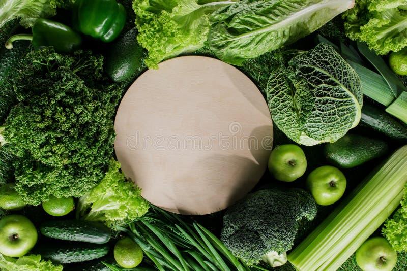 hoogste mening van ronde houten raad tussen groene groenten, gezond het eten concept royalty-vrije stock afbeelding