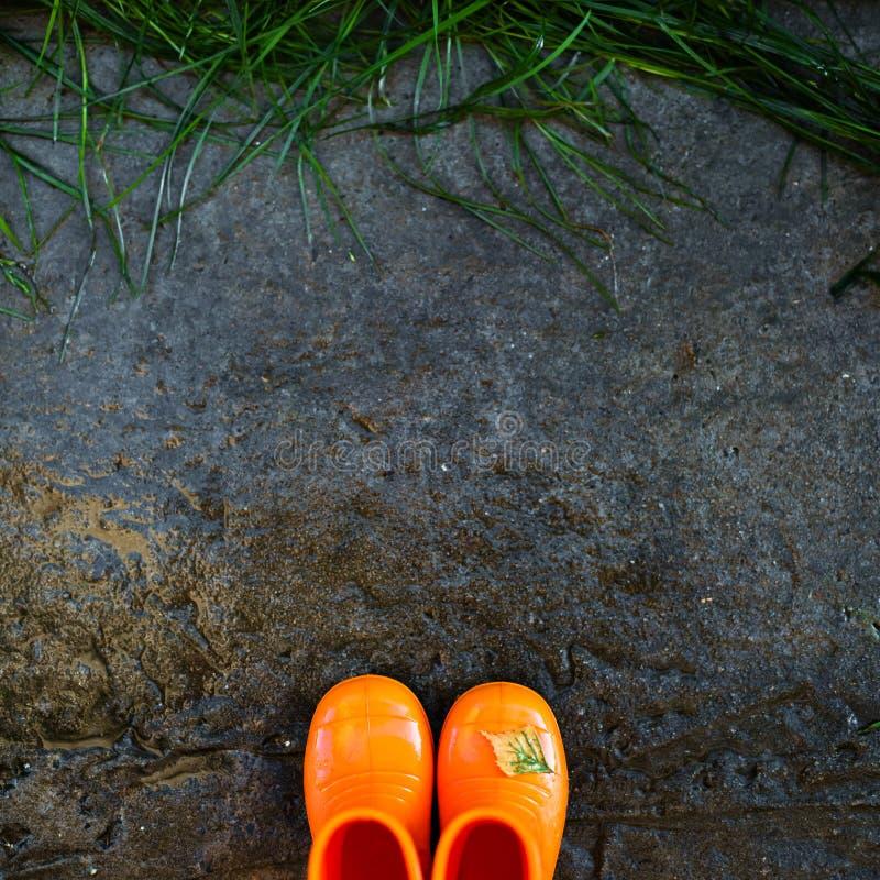 Hoogste mening van roodachtige rubberlaarzen op natte concrete achtergrond voor het natte groene gras stock afbeeldingen