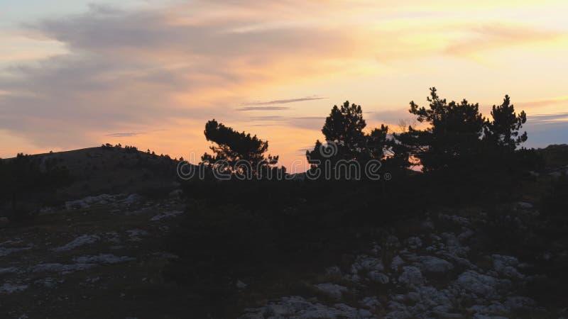Hoogste mening van rotsachtige bovenkant op achtergrond van zonsondergangkleuren met wolken schot Kleurrijk schilderachtig landsc royalty-vrije stock afbeelding