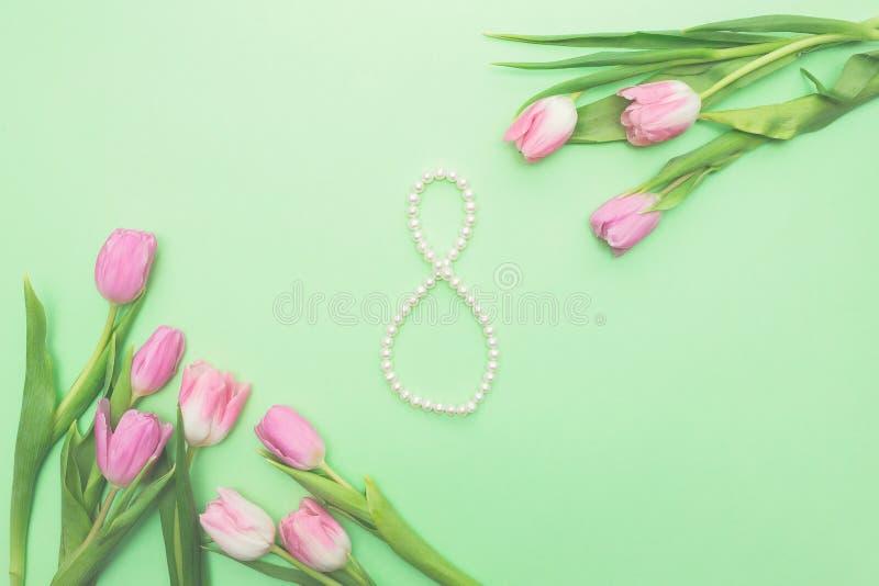 Hoogste mening van roze die tulpen en figuur acht van koord van parels op lichtgroene achtergrond met exemplaarruimte worden gema stock fotografie