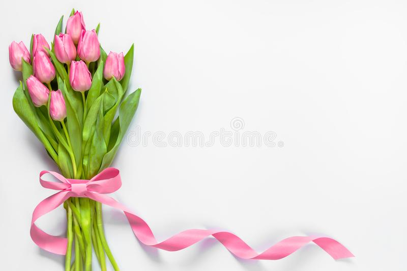 Hoogste mening van roze die tulpenboeket, met roze lint over witte achtergrond wordt verpakt De ruimte van het exemplaar stock foto