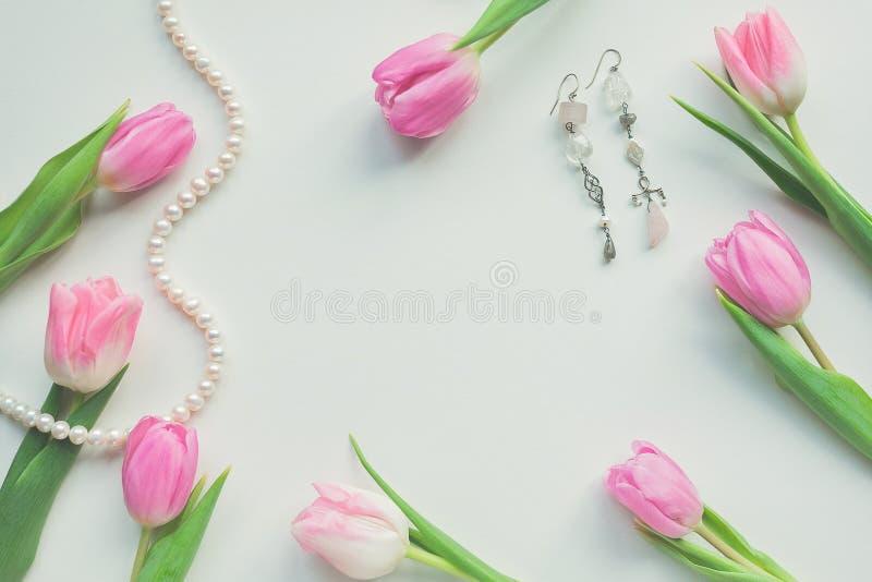 Hoogste mening van roze tulpen, oorringen en koord van parels op witte achtergrond met exemplaarruimte Mooie de lenteachtergrond  royalty-vrije stock afbeelding