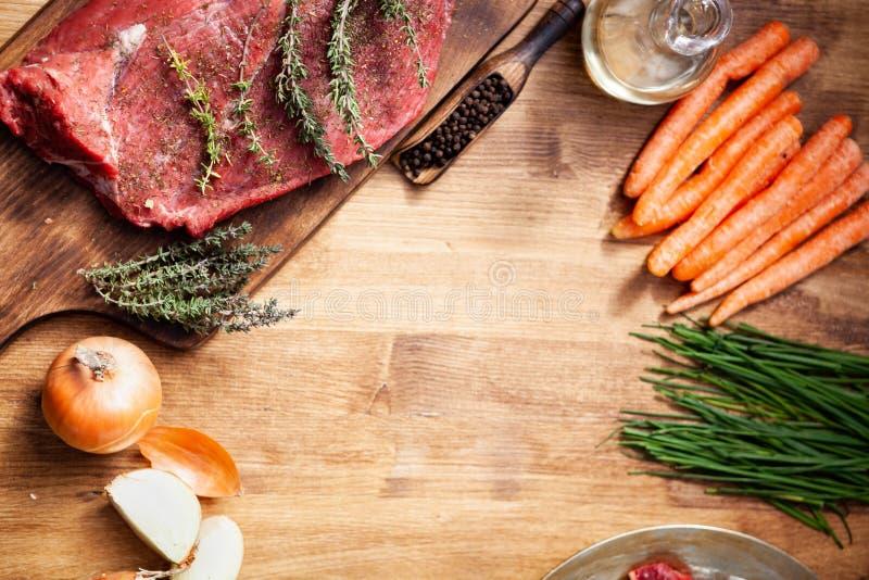 Hoogste mening van ruw vlees en gezonde ingrediënten voor barbecue op houten lijst stock afbeeldingen