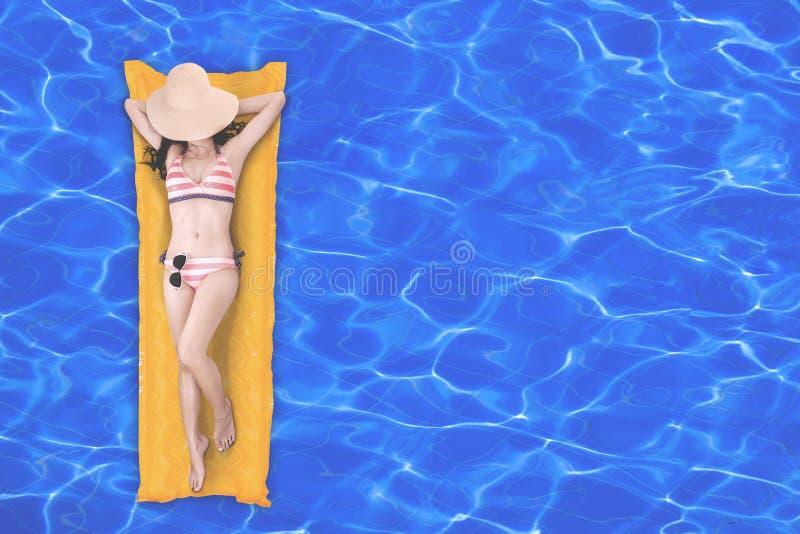Hoogste mening van slanke jonge vrouw in bikini het ontspannen op de gele luchtmatras in zwembad stock foto