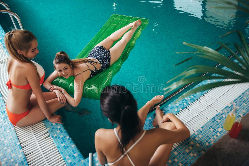 Hoogste mening van slanke jonge vrouwelijke vrienden die bij hotel zwembad ontspannen royalty-vrije stock afbeeldingen
