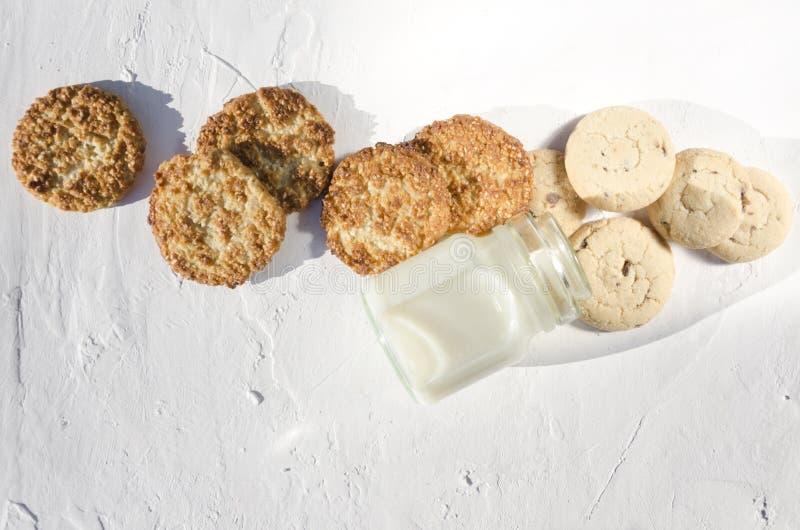 Hoogste mening van smakelijke koekjes met chocolade en sesam, glasfles van verse melk op de witte rustieke lijst, empry ruimte vo royalty-vrije stock fotografie