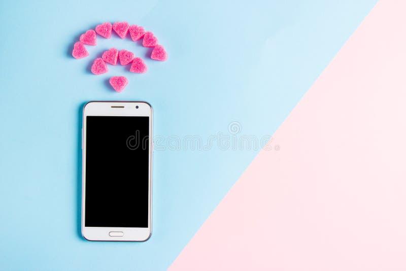 Hoogste mening van smartphone met het symbool van Wi FI van decoratieve harten op kunst blauwe en roze document achtergrond De te stock fotografie