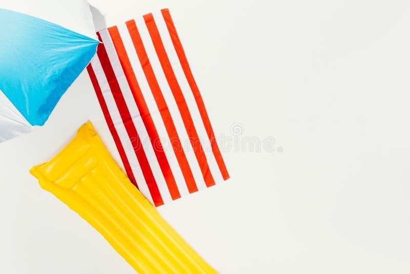 hoogste mening van strandparaplu, gestreepte handdoek en opblaasbare matras stock foto