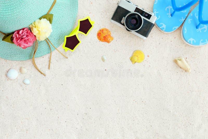 Hoogste mening van strandzand met strohoed, zonnebril, shells, camera, pantoffels en koraal stock afbeelding