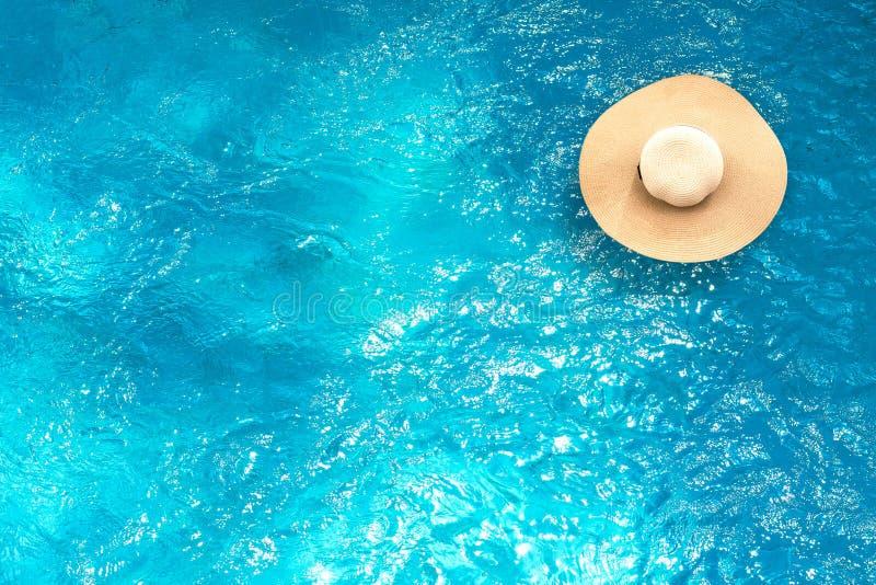 Hoogste mening van strohoed die op zwembad met de zomerachtergrond drijven Vakantietijd of Vakantielevensstijl stock afbeeldingen