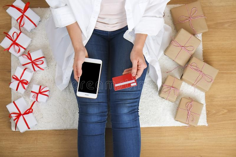 Hoogste mening van studentenmeisje die Internet surfen, online winkelend op laptop en cellphone, houdend debet/creditcard, ingaan stock afbeelding