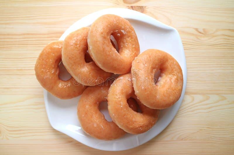 Hoogste mening van suiker-verglaasde die doughnuts op witte plaat op houten lijst worden gediend royalty-vrije stock afbeelding