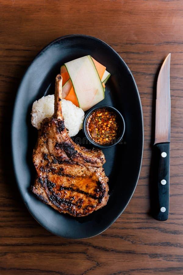 Hoogste mening van Thaise stijlbbq Varkenskotelet die met kleverige rijst, gesneden wortel en Thaise kruidige saus wordt gediend  royalty-vrije stock foto