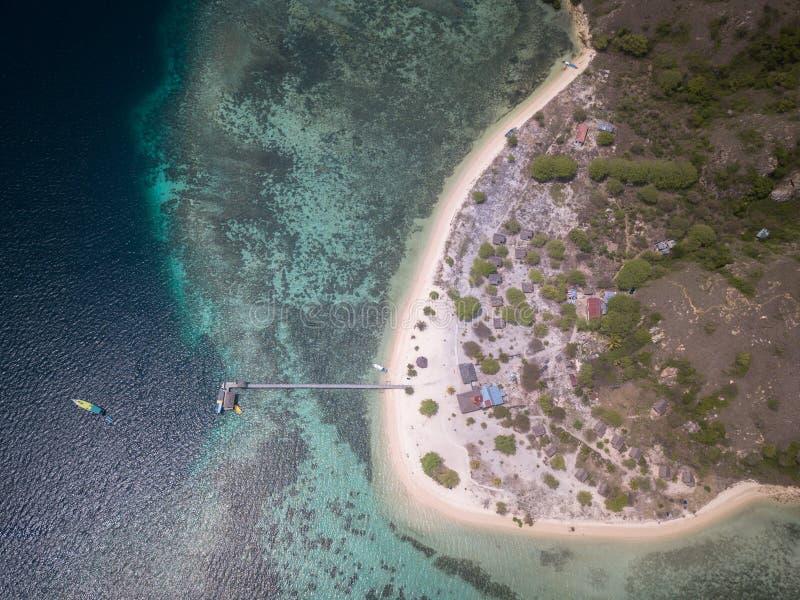 Hoogste mening van toeristenschip en pier in het Kanawa-eiland, het Oosten Nusa Tenggara, Indonesië royalty-vrije stock afbeeldingen
