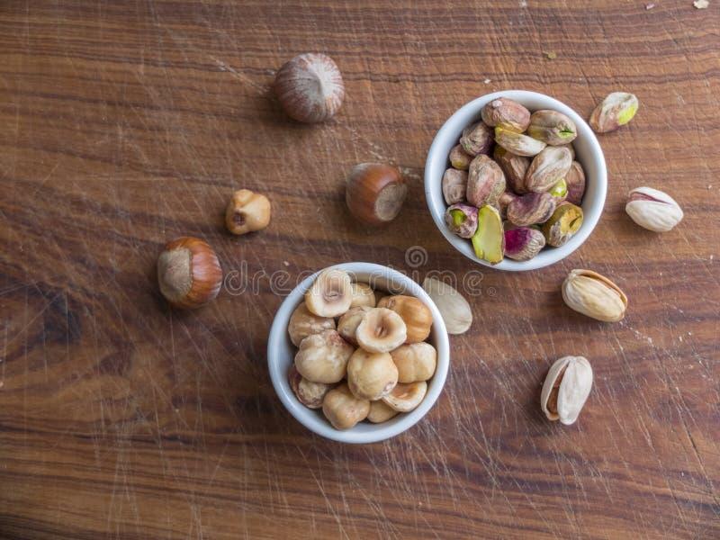 Hoogste mening van twee ceramische koppen die geroosterde en gepelde hazelnoten en één van pistaches bevatten stock foto's
