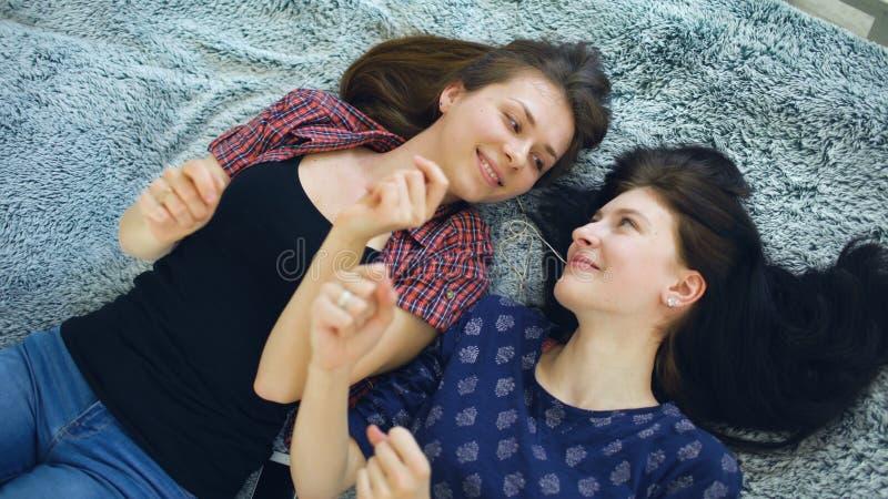 Hoogste mening van twee mooie meisjes in hoofdtelefoons het luisteren en muziek die terwijl het liggen op bed dansen glimlachen stock afbeeldingen
