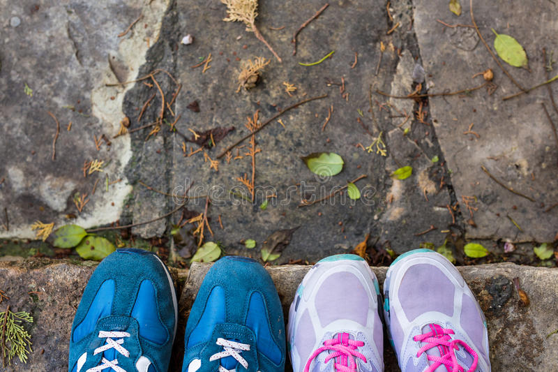 Hoogste mening van twee paren tennisschoenenschoenen op straatsteen stock afbeelding