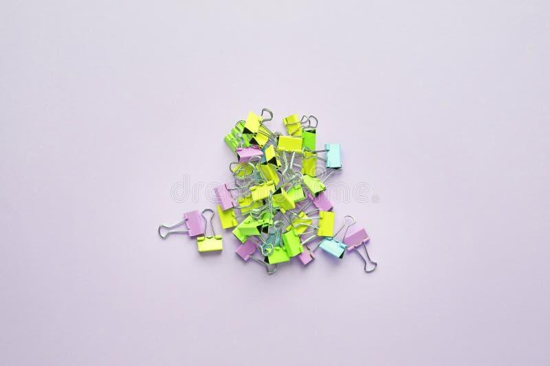 Hoogste mening van vele veelkleurige bindmiddelenklemmen op pastelkleur purpere achtergrond stock afbeelding