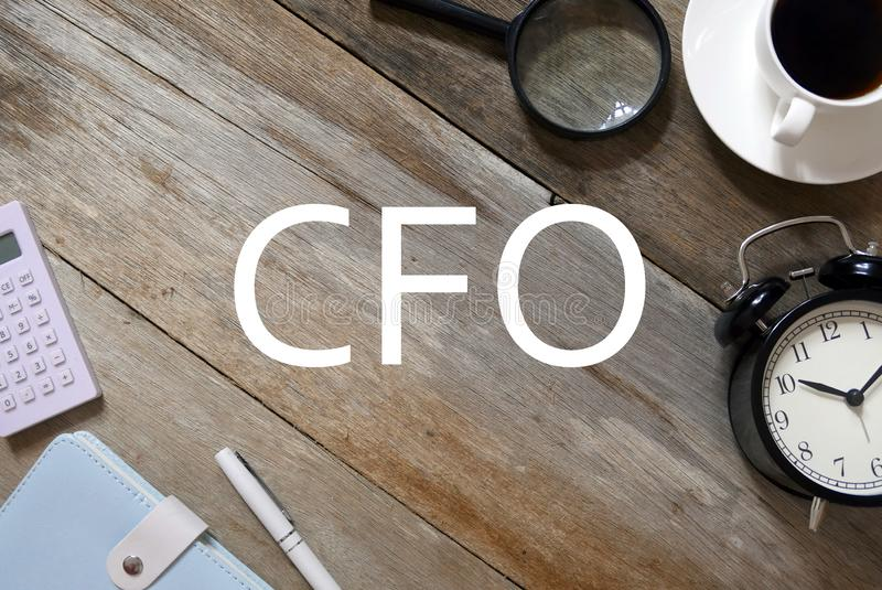 Hoogste mening van vergrootglas, een kop van koffie, klok, pen, notitieboekje en calculator op houten die achtergrond met CFO wor royalty-vrije stock foto