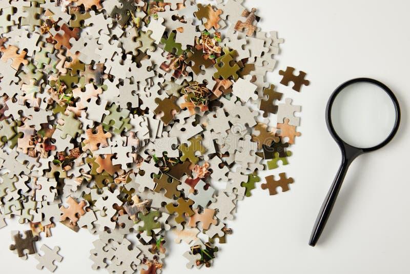 hoogste mening van vergrootglas en puzzelstukken op grijs royalty-vrije stock afbeelding