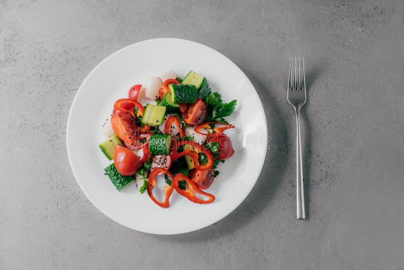 Hoogste mening van verse die groentesalade van Spaanse peper, radijs, tomaten, komkommers en peterselie in witte kom, vork dichtb royalty-vrije stock fotografie