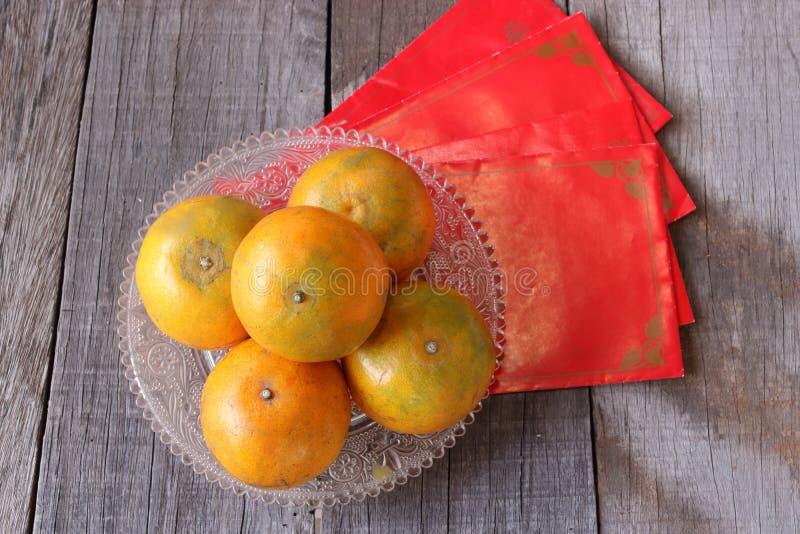 Hoogste mening van verse sinaasappelen in een kom op oude houten raad met Chinese rode enveloppakket of ANG-paoachtergrond Gelukk royalty-vrije stock foto's