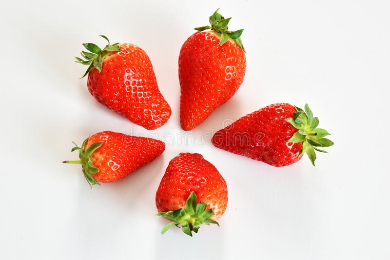 Hoogste mening van vier aardbeien op wit vliegtuig royalty-vrije stock afbeelding