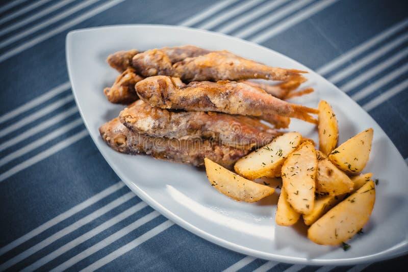 Hoogste mening van vis met patat Gebraden vissen en aardappelplakken op een witte plaat Plaat op de lijst met een blauw binnen ta royalty-vrije stock afbeeldingen