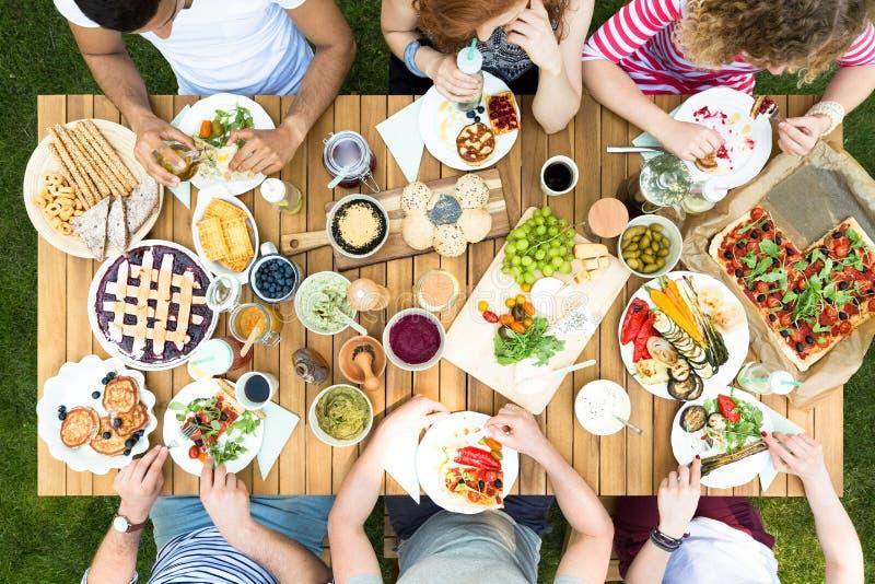 Hoogste mening van vrienden die bij de lijst zitten en Italiaans voedsel eten stock fotografie