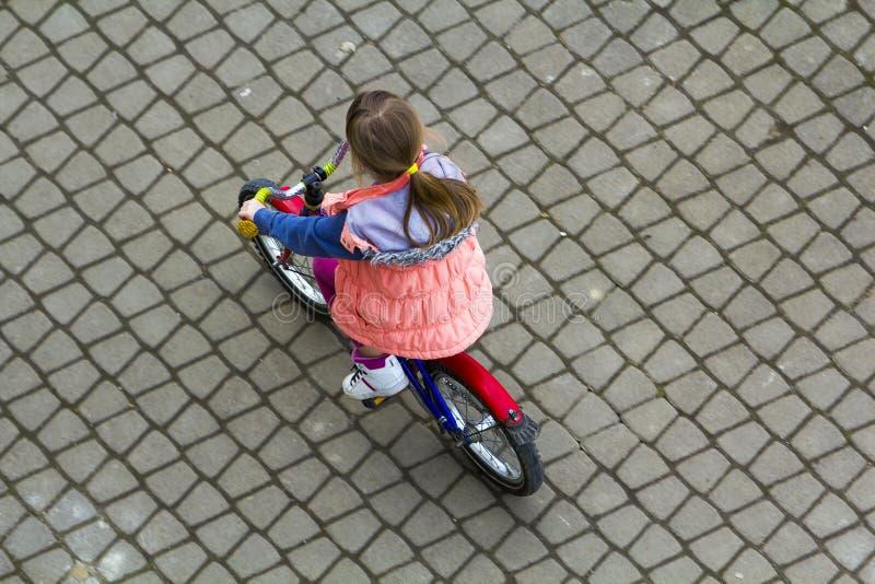Hoogste mening van vrij jong meisje met lang lichtbruin haar die een fiets berijden op koele de lentedag die stijgend kijken In o royalty-vrije stock foto