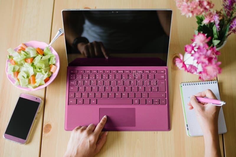 Hoogste mening van vrouw gebruikend computerlaptop en nemend nota's over een nr stock afbeelding
