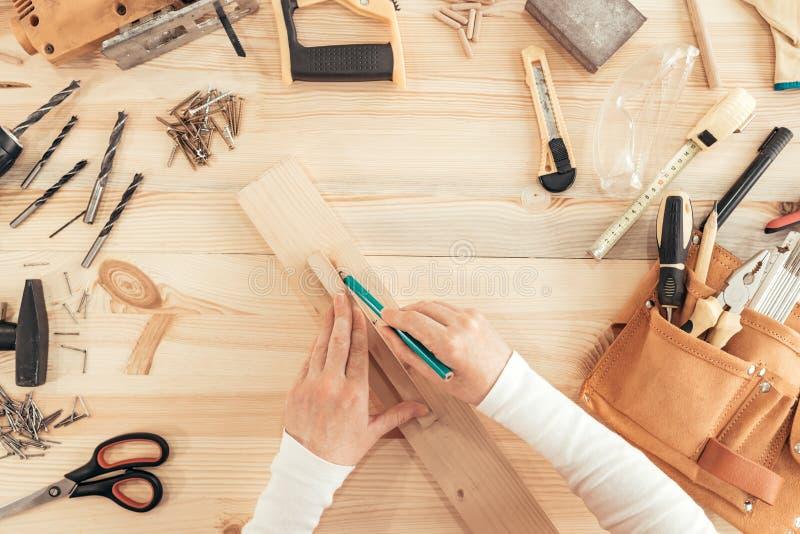 Hoogste mening van vrouwelijke timmermanshanden die aan bureau werken stock foto's