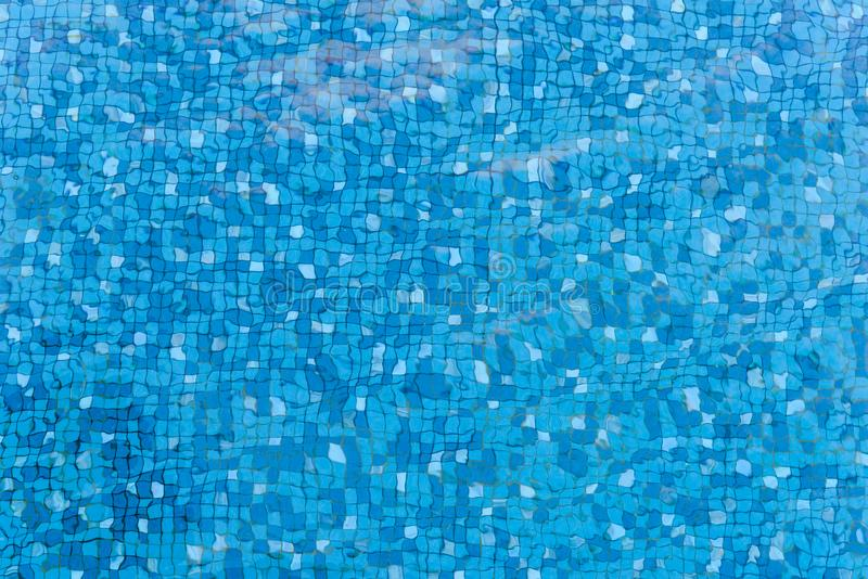 Hoogste mening van waterrimpelingen op blauw betegeld mozaïek Bodem van zwembad Achtergrond stock fotografie