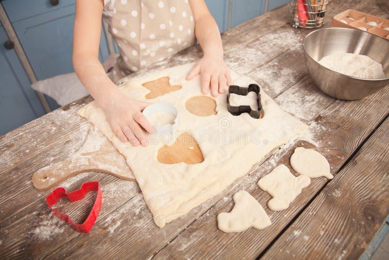 Hoogste mening van weinig kindmeisje die haar moeder in de keuken helpen om koekjes te maken makend verschillende vormen van koek royalty-vrije stock foto's