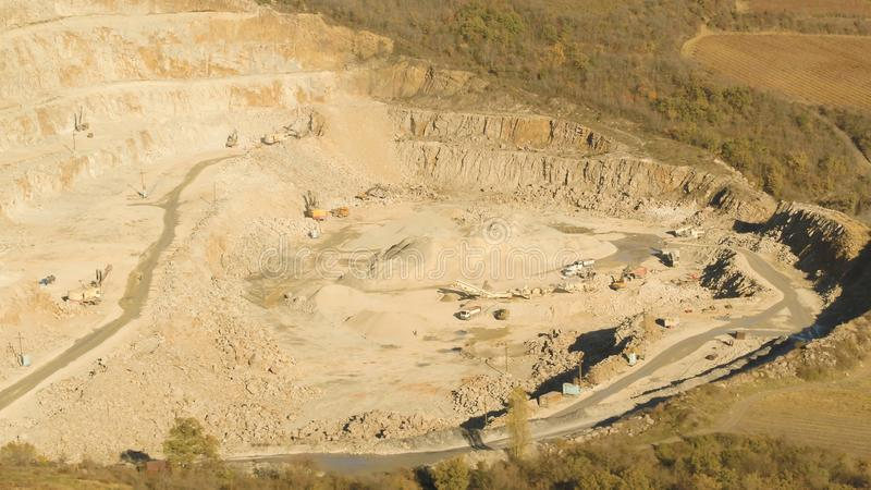 Hoogste mening van werkende steengroeve schot Zandkuil met roltrappen en buldozeri in open bos Het concept van de mijnbouw royalty-vrije stock fotografie
