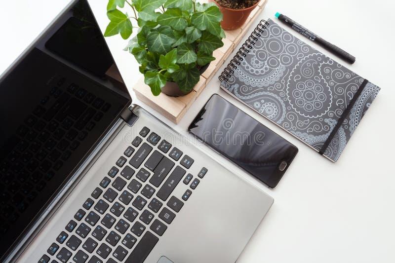 Hoogste mening van wit bureau met laptop, smartphone en installaties Hoogste mening met exemplaarruimte royalty-vrije stock afbeelding