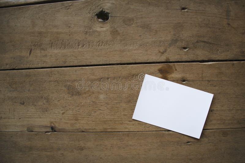 Hoogste mening van wit prentbriefkaar of document op oude houten achtergrond stock afbeelding