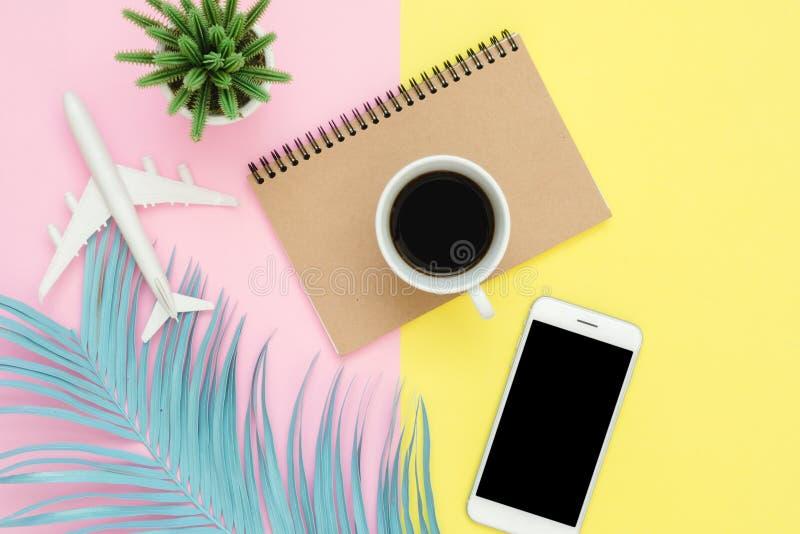 Hoogste mening van Witboeknotitieboekje, pen, spot op smartphone, blauw blad, koffie en vliegtuig op roze gele pastelkleur stock fotografie