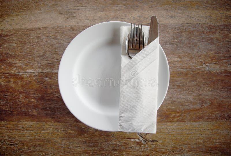 Hoogste mening van witte cirkelplaat met lepel, vork, mes en servet op houten lijst stock afbeeldingen