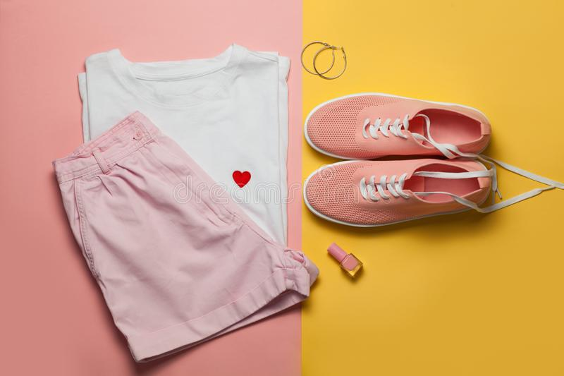 Hoogste mening van witte vrouwent-shirt en roze schoenen op roze en gele achtergrond Geplaatste manierkleren en toebehoren Vlak l royalty-vrije stock foto's
